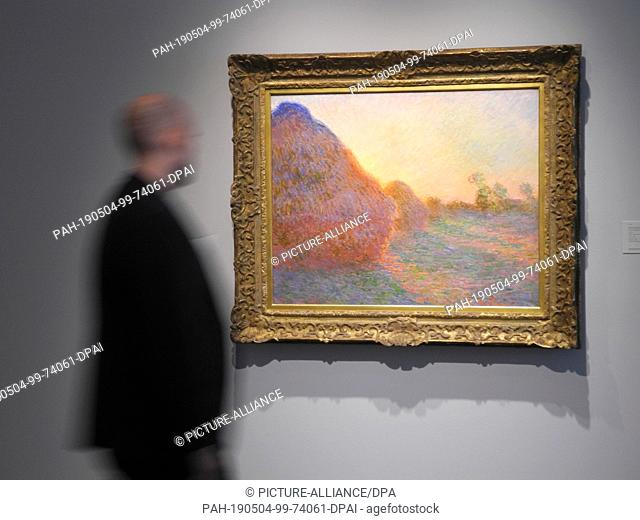 """03 May 2019, US, New York: At Sotheby's, a visitor looks at Claude Monet's painting """"""""Meules"""""""". The auction house Sotheby's has reopened its converted galleries..."""