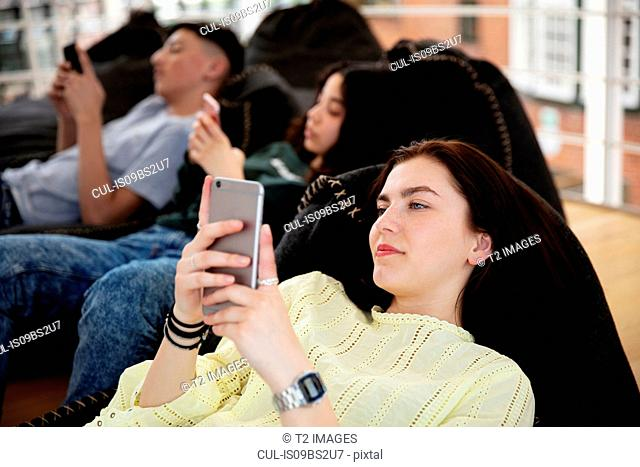 School friends lying on beanbags and texting at school