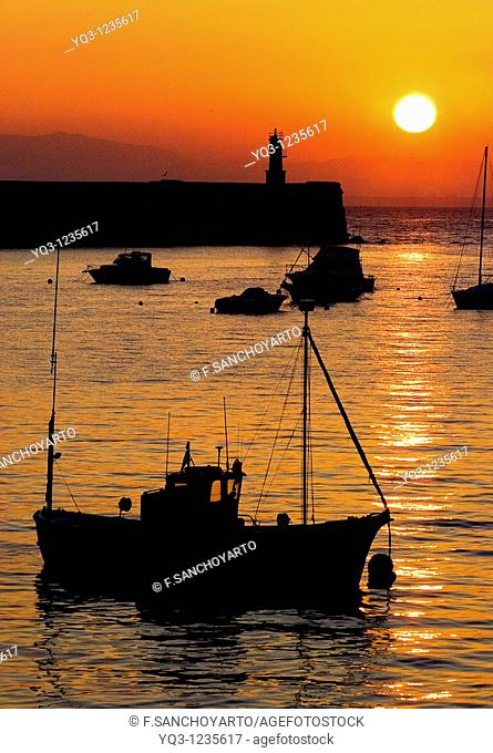 Sun rising over breakwater. Port of Castro Urdiales , Cantabria, Spain