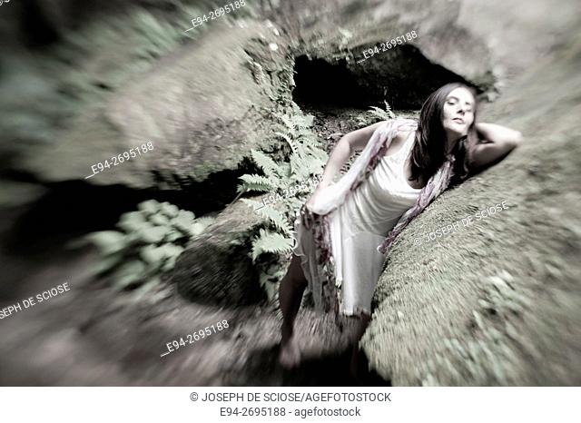 A partially nude 42 year old brunette woman wearing a white dress and leaning next to a rock in a forest, black and white