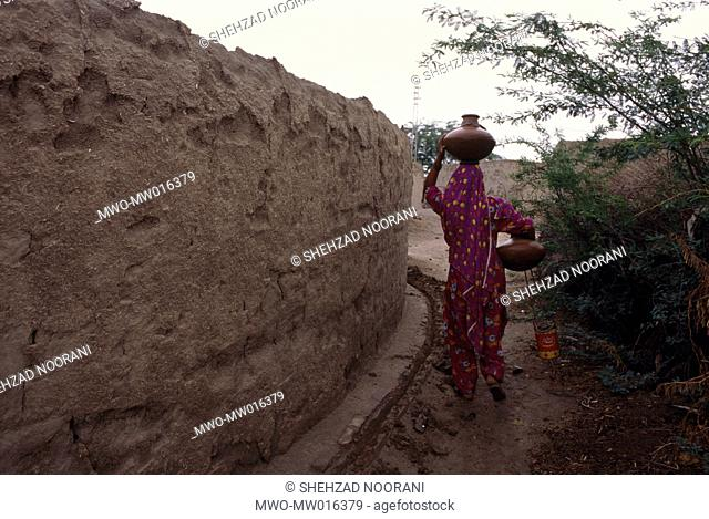 A woman carrying water in traditional earthen pottery, in a village, in Omerkot, Sindh province, Pakistan April 26, 2005