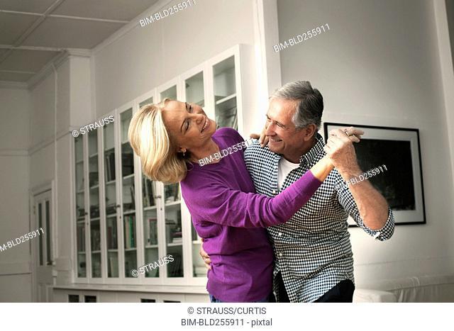 Smiling Caucasian couple dancing in home