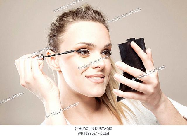 Young woman applying mascara