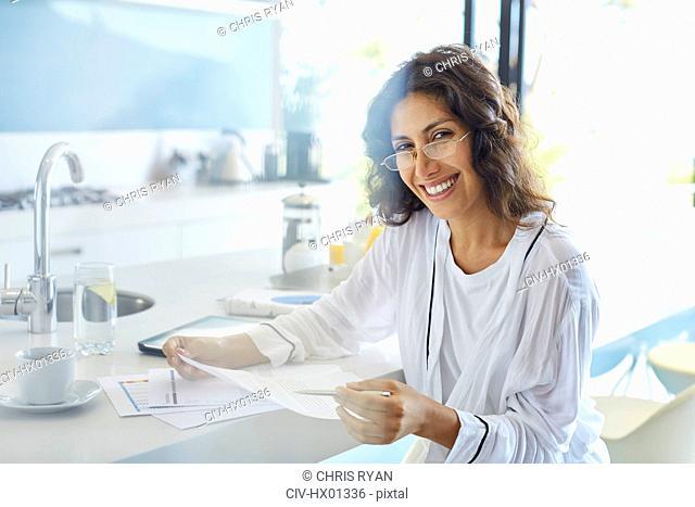 Portrait smiling businesswoman in bathrobe reviewing paperwork in kitchen
