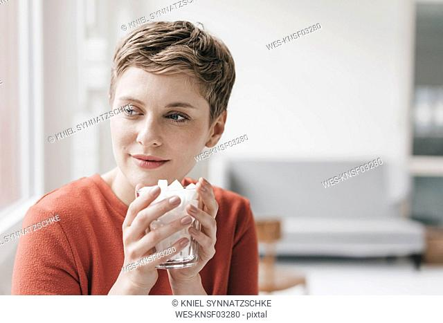 Smiling woman holding glass full of sugar cubes