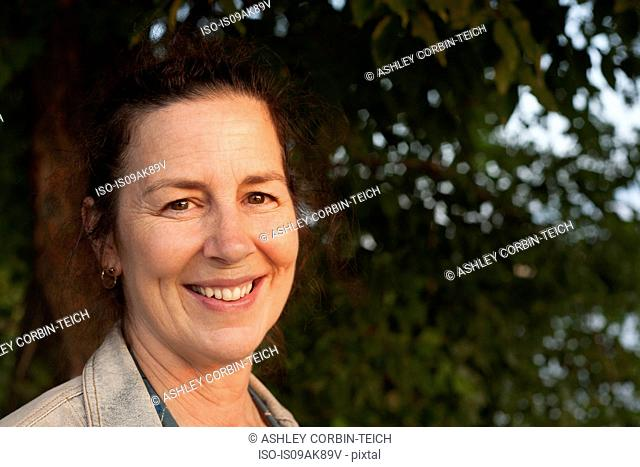 Portrait of smiling mature woman in woodland