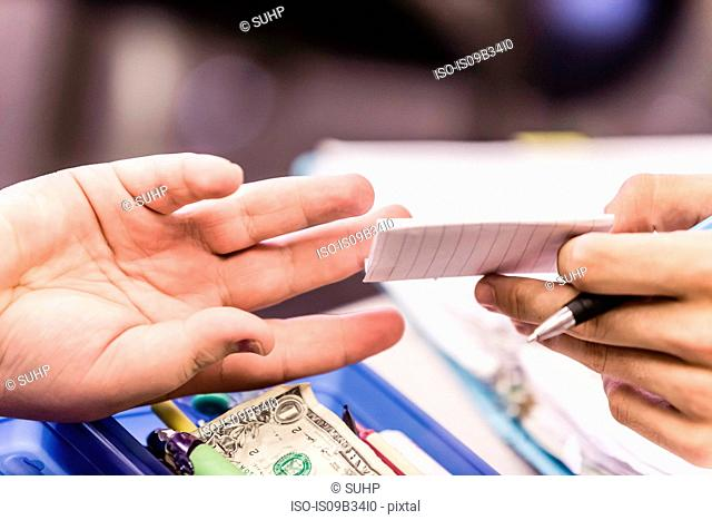 Close up of hands handing note at desk in high school lesson