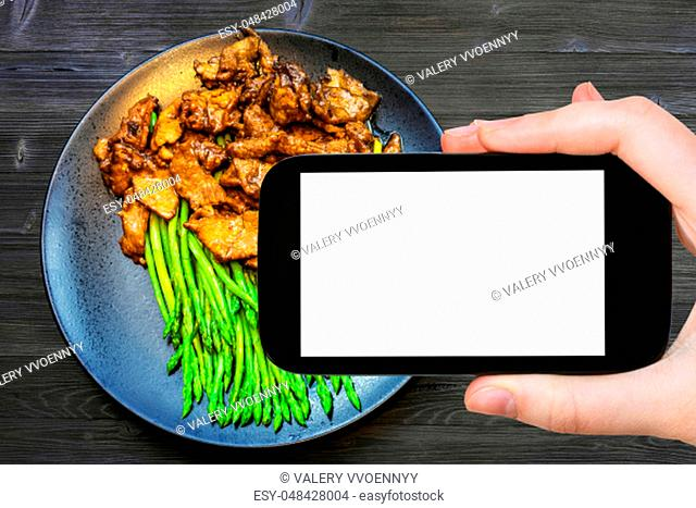 travel concept - tourist photographs of Chinese cuisine dish of Beef fried in soy sauce with green asparagus on smartphone with empty cutout screen with blank...