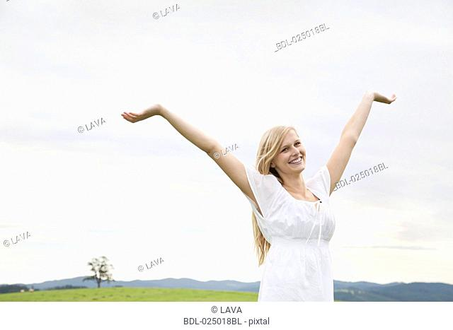 young woman on meadow raising her arms in the air