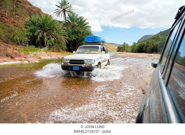 Cars driving in shallow river in tropical landscape