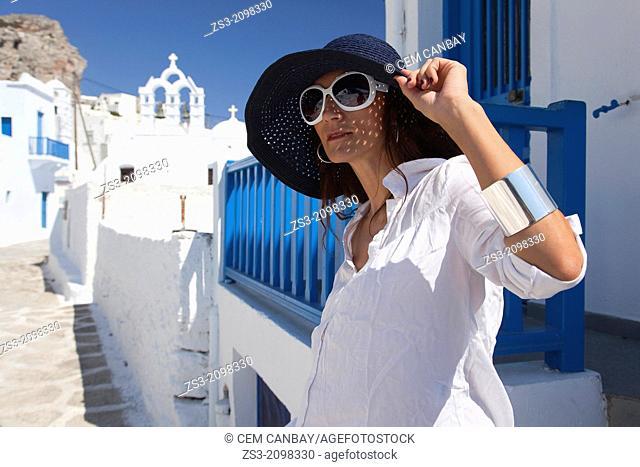 Woman posing in Chora near a church, Amorgos, Cyclades Islands, Greek Islands, Greece, Europe