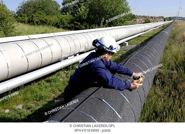 MODEL RELEASED. Worker checking gas pipeline