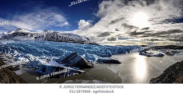 Blue ice of the Svinafellsjokull glacier flowing from the mountains to a small lagoon