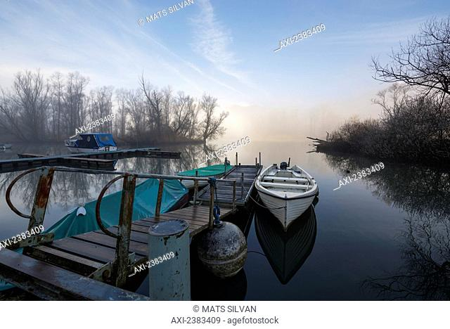 Mist rising over Lake Maggiore with a canoe tethered to a dock; Locarno, Ticino, Switzerland