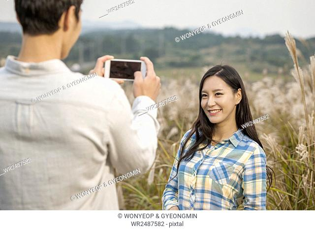 Portrait of young smiling woman posing and man taking picture of her with a camera in silver grass field