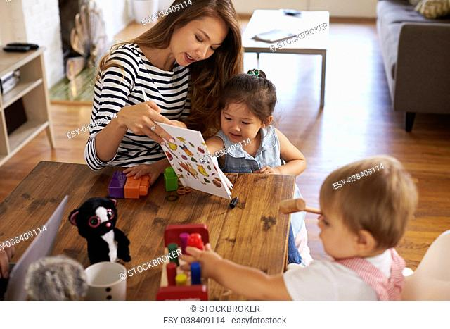 Mother Playing With Children On Table At Home