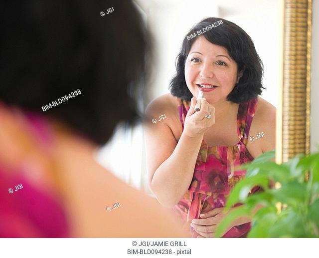 Hispanic woman putting on lipstick