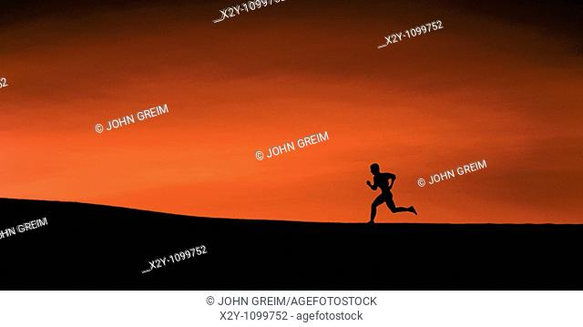 The silhouette of a man running up a slight incline, high contrast of land, figure and crimson sky
