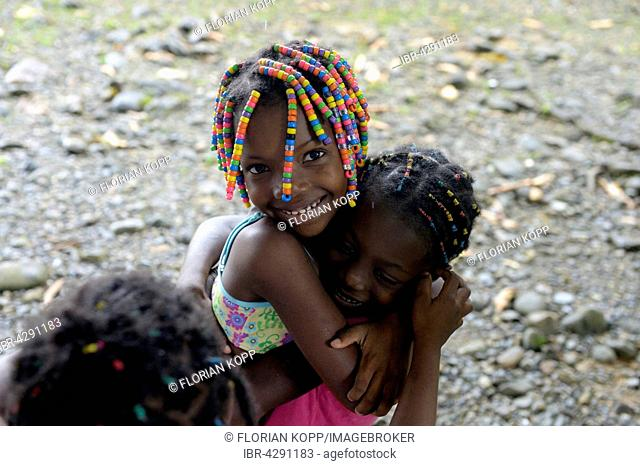 Two girls hugging each other, afro-columbian village of Playa Bonita on the river Rio Andagueda, Chocó Department, Colombia