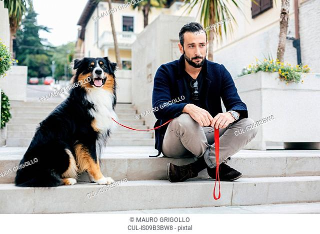 Mid adult man sitting on stairway with pet dog in city square