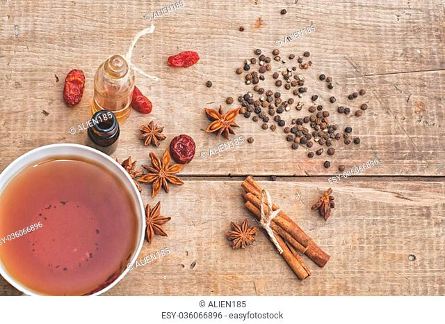 Tea, dried cinnamon, pepper and anise on wooden background
