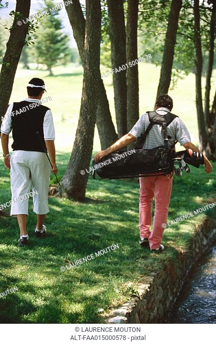 Golfers looking for ball under trees, rear view