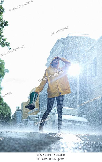 Woman in raincoat carrying wellingtons and walking barefoot in rain
