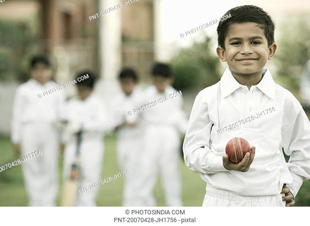 Cricketer holding a cricket ball and smiling