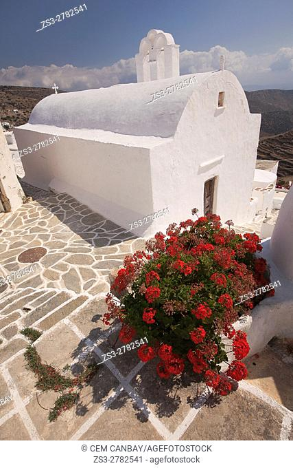 Whitewashed church with geraniums in the foreground at the old town Chora or Chorio, Sikinos, Cyclades Islands, Greek Islands, Greece, Europe