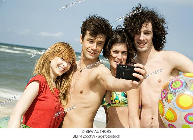 Four friends taking picture on the beach