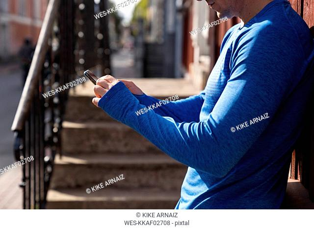 Close-up of athlete leaning against house wall using cell phone