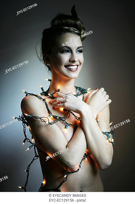 Portrait of happy nude woman wrapped in Christmas lights, studio shot