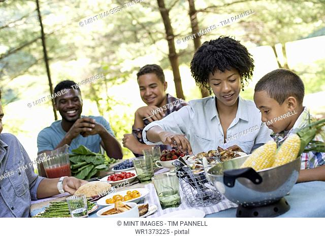 A family picnic in a shady woodland. Adults and children around a table handing around plates and food