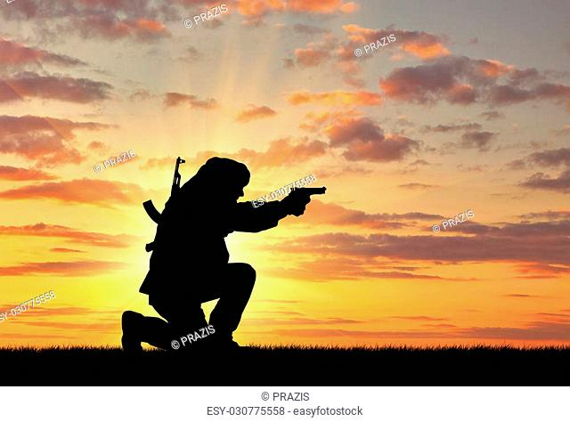 Concept of terrorism. Silhouette of a terrorist with a rifle on a background of sunset