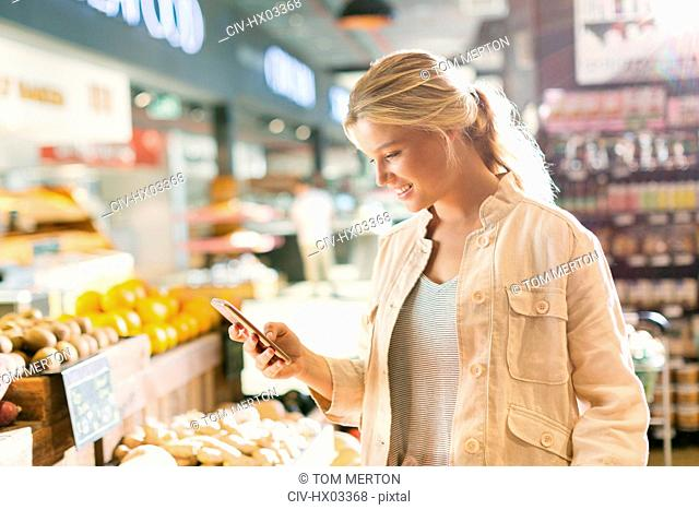 Young woman using cell phone in grocery store market