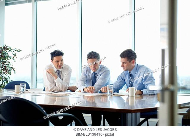 Businessmen talking in office meeting