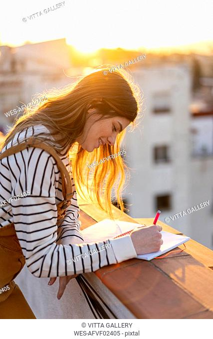 Smiling young woman taking notes on roof terrace at sunset
