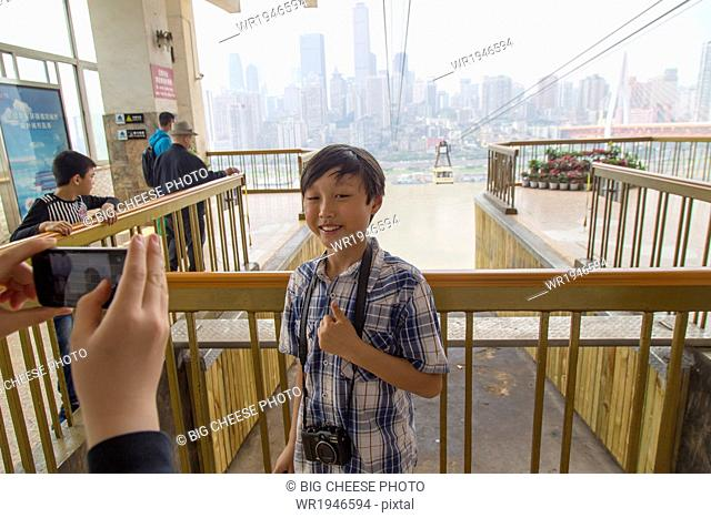 Boy being photographed in front of a Yangtze cable car
