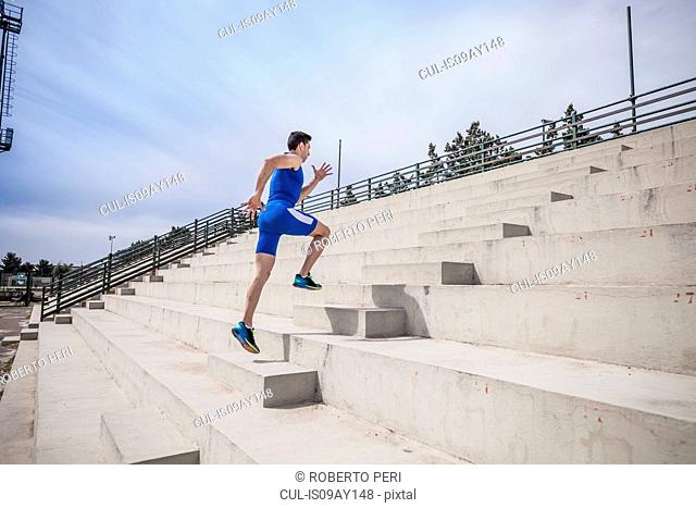 Young male runner running up stairway