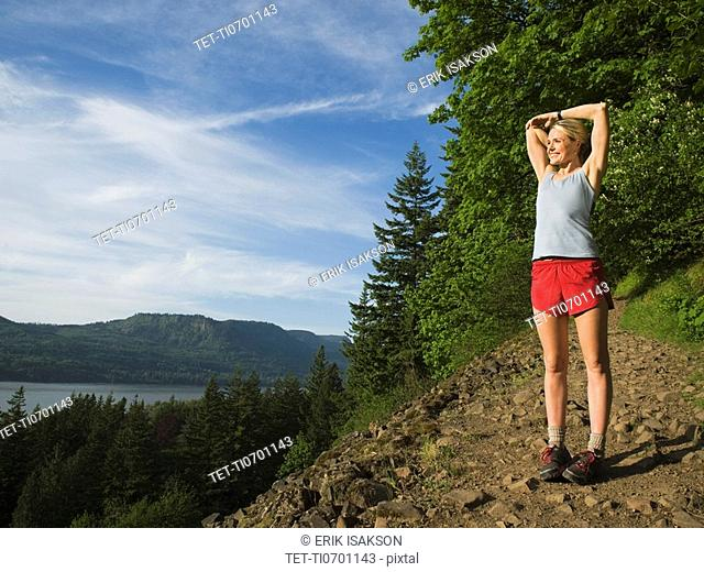 Runner stretching on rocky trail