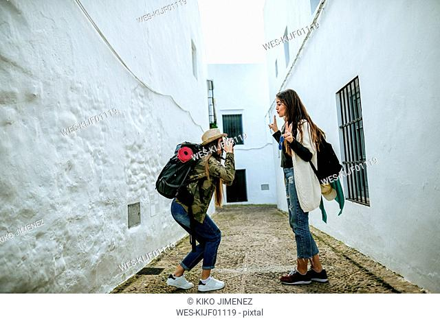 Young traveling women taking photos in a town
