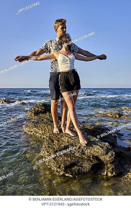 Couple standing on rocks, holding hands, bonding, seaside, holiday, love, lovers. Chersonissos, Crete, Greece