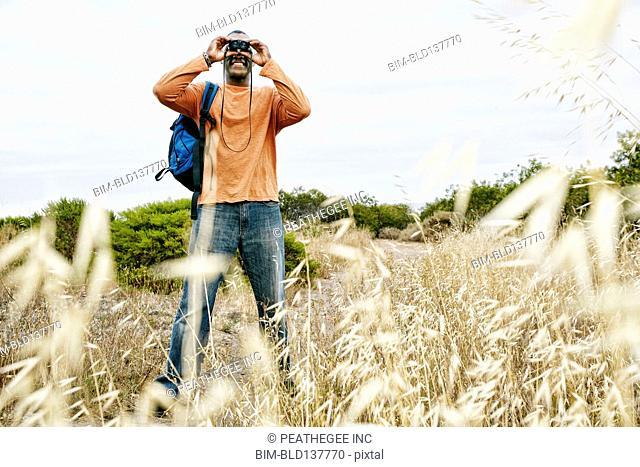 Black man hiking on rural hillside