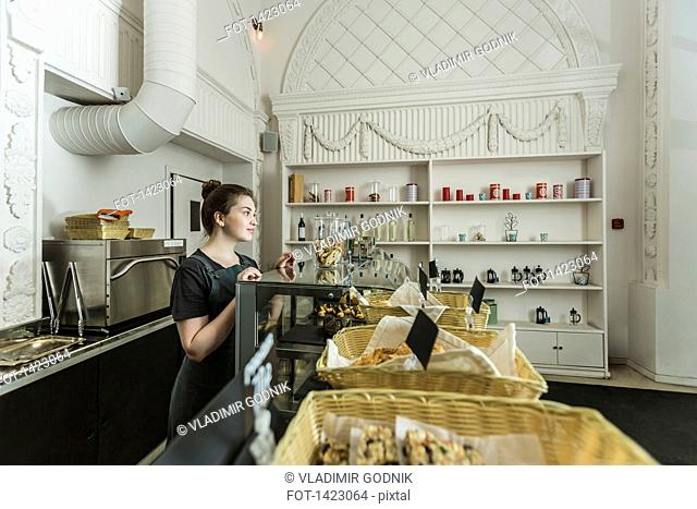 Young woman behind cafe counter