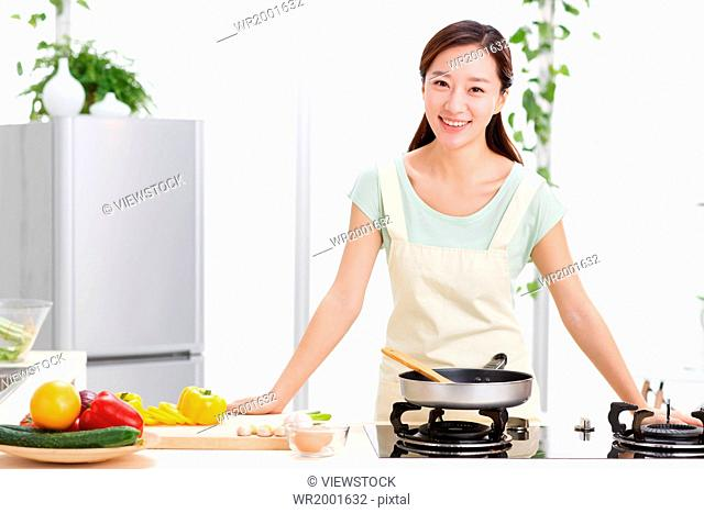 Young woman cooking in kitchen