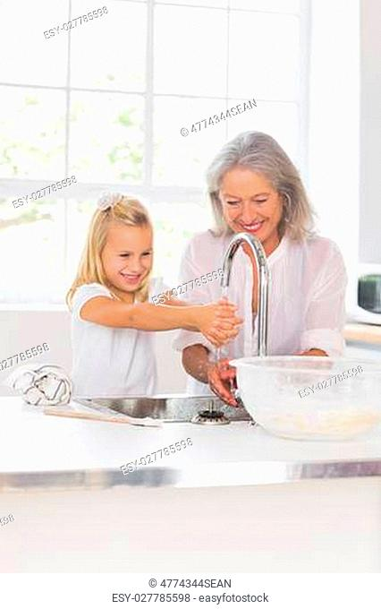 Happy grandmother and granddaughter washing hands in the kitchen