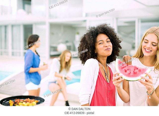 Women eating watermelon at barbecue