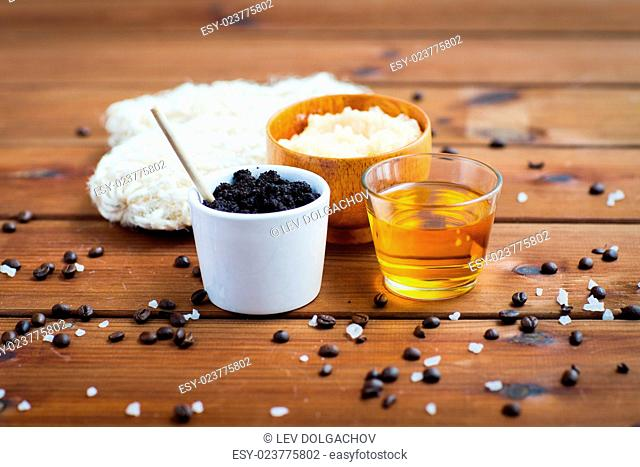 beauty, spa, body care, bath and natural cosmetics concept - close up of coffee scrub in cup and honey on wooden table