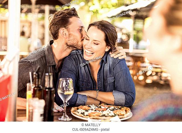 Couple at sidewalk cafe kissing