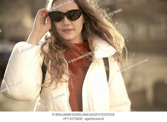 young cool woman, hand touching sunglasses, in city Cottbus, Brandenburg, Germany